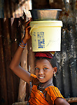 A girl carries water in a bucket in Sonougouba, Mali, where the ACT Alliance has worked with local residents to encourage a sustainable economy, increase food security, and improve local governance.