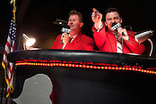 "Wundamike, left, and Wesley Page, known as the ""redcoats"" call the bout from the announcers stand during a bout between Hellcats and Putas del Fuego at the Palmer Events Center in Austin, Texas."
