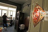Li Fang et Gao Cuilan préparent le déjeuner tandis que le caractère chinois fu (« bonheur ») orne la porte de leur cuisine, à Baoshan, près de Shanghai, le 7 mai 2008. Lorsqu'il est placé ainsi la tête en bas, il est censé amener le bonheur dans la maison. Comme dans chaque cuisine chinoise, on trouve aussi debout contre le mur une table ronde de banquet... ce qui permet d'agrandir la table pour les grandes occasions et les dîners familiaux. Photo par Lucas Schifres/Pictobank
