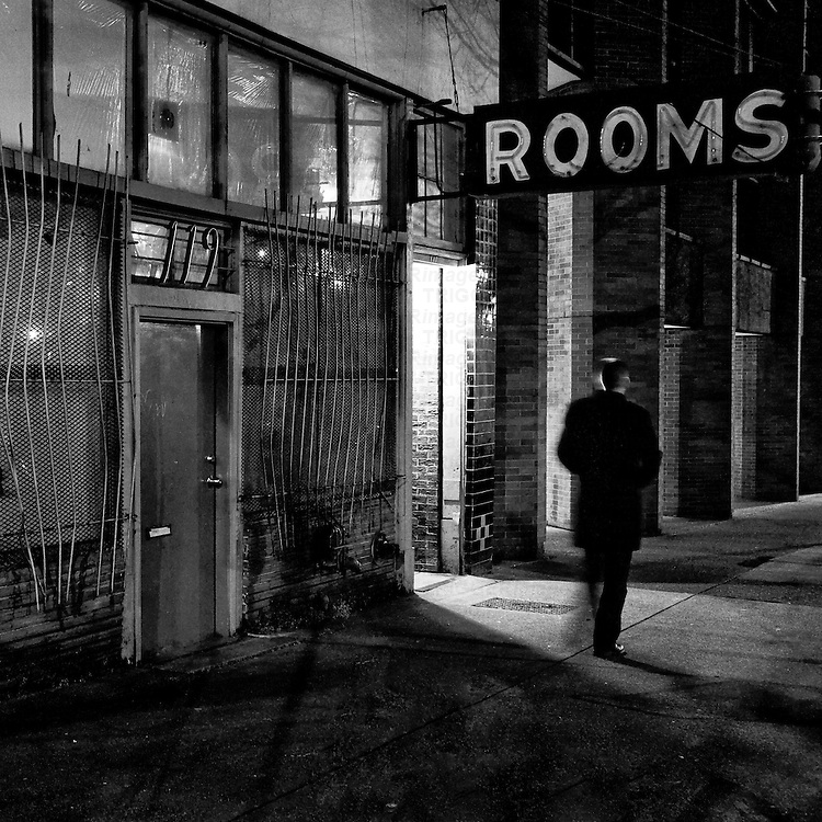 A lone man walking down an abandoned street passing decaying buildings on the lower east side of Vancouver Canada