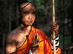 Artistic portrait of a Shaolin warrior monk with a staff in a forest holding a one hand greeting or Amituofo gesture