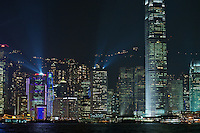 The skyscrapers of Hong Kong's Central district lit up at night, with laser searchlights for the nightly Symphony of Lights show