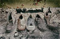 Five single shoes belonging to ex-patients at the derelict West Park Asylum, Epsom, Surrey, processed to emulate wet plate technique.