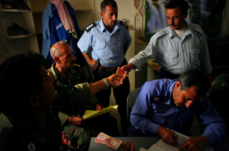 Iraqi policemen - most little more than raw untrained recruits -  draw their pay at a station in the Ramadi suburb, Tameem, on Sunday May 20, 2007. One of the most serious threats to the continuance of the newly created force is whether or not the Shiite-led government in Baghdad is willing to ensure that funds and equipment flow to Ramadi and the rest of Anbar.