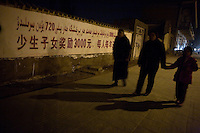 People walk past a government billboard about money offered to Uighur families who have fewer children.  The text reads, approximately, &quot;Having fewer children rewards 3000yuan (about $450), that's 720yuan ($110) a person a year.&quot;