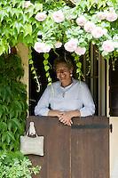 Portrait of Grazia Adamo Giovannetti standing at the half open stable door of her rose garden Ca' delle Rose