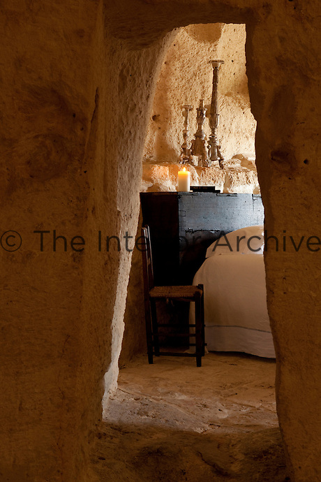 View through a narrow doorway of one of the bedrooms at the unique Albergo Diffuso Le Grotte della Civita in Southern Italy housed in restored caves
