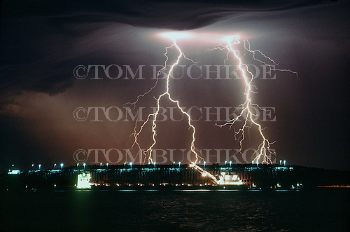 Lightning strikes just North of the M/V H Lee White as it loads taconite iron ore pellets at the LS&I ore dock in Marquette, Michigan on Lake Superior.