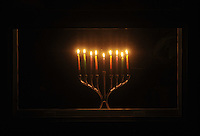 """Photo Illustration  NWA Democrat-Gazette/MICHAEL WOODS • After the menorah is lit on Hanukkah, the 8-day Jewish festival of light, it is traditionally placed in the window for the world to see.  Hanukkah celebrates religious freedom and the triumph of light over darkness. Hanukkah means """"dedication"""" and refers to the rededication of the Holy Temple in Jerusalem at the end of the war.  Hanukkah is observed for eight nights and days, starting on the 25th day of Kislev according to the Hebrew calendar."""