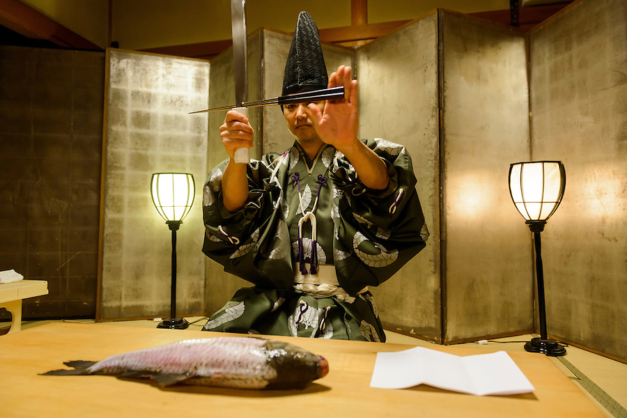 """Ikama Masayasu prepares a carp in a """"shikibocho"""" Imperial Knife Ceremony, Ginza Restaurant, Asakuchi City, Okayama Pref, Japan, January 28, 2014. Ikama Masayasu is 29th head of the Kyoto Ikama school of shikibocho. Shikibocho is a Shinto ceremony in which raw fish or fowl is filleted using only a knife and chopsticks. During the ceremony which dates back to the Japanese Imperial Court of 859 the master does not touch the fish with his hands."""
