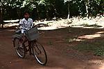 A girl rides her bicycle at Angkor Wat, Cambodia. June 7, 2013.