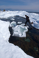 A snowshoer jumps on ice formations floating on Lake Superir at the tip of the Keweenaw Peninsula near Copper Harbor, Michigan.