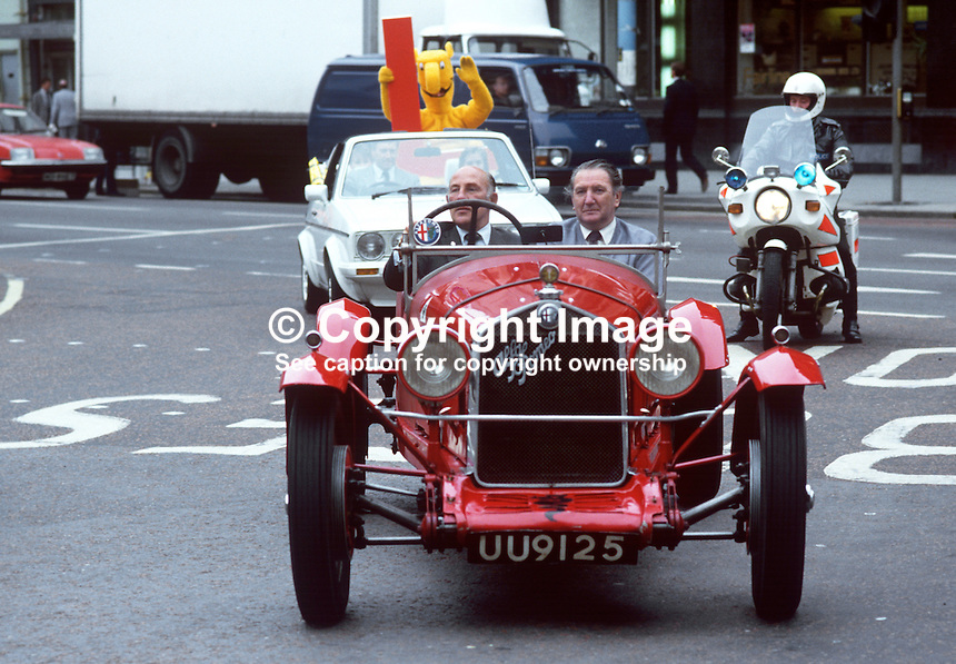 Former Formula 1 racing driver Stirling Moss, UK, drives a vintage Alfa Romeo Campari, in Belfast city centre during a visit to N Ireland. His passenger is Ballymena garage owner, Malcolm Templeton. 19850713SM2<br />