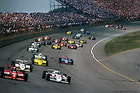 BROOKLYN, MI - JULY 22: The start of the Michigan 500 on July 22, 1984, at the Michigan International Speedway near Brooklyn, Michigan. Fastest qualifier and race winner Mario Andretti (#3) leads, followed by Tom Sneva (#4), Bobby Rahal (#5), Rick Mears (#6), Gordon Johncock (#20), and the rest of the field.