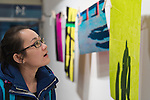 Huntington, New York, U.S. - March 1, 2014 - A young woman visitor at the Opening Reception '3 Wild and Crazy Artists' at FotoFoto Gallery looks at colorful artwork by artist Thom O'Connor in his exhibit 'Hung Out To Dry.'