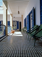 View along the covered terrace with a black and white check tiled floor and row of green wicker chairs