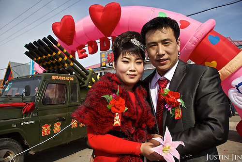 A couple weds in Chagangcheng, a township  50 km from Manzhouli which is on the Russian-Chinese border. The fake rocket launcher in the background emits fireworks.