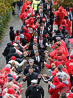 Ohio State Buckeyes head coach Urban Meyer, bottom, and his players celebrate with fans as they make their way into Ohio Stadium before the NCAA football game between the Ohio State Buckeyes and the Iowa Hawkeyes in Columbus, Saturday afternoon, October 19, 2013. (The Columbus Dispatch / Eamon Queeney)