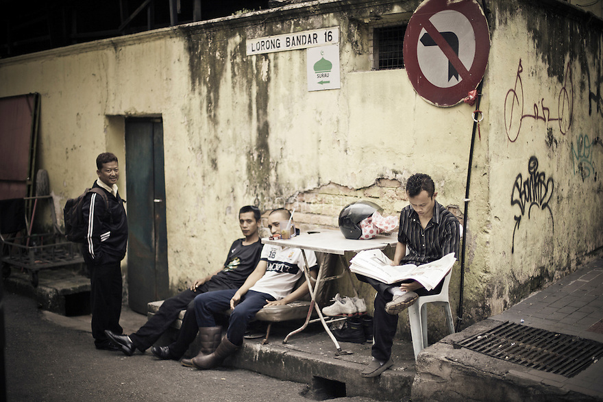 Young men relaxing on the street, Kuala Lumpur