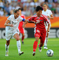 Christie Rampone (l) of Team USA and Kwon Song Hwa of Team North Korea during the FIFA Women's World Cup at the FIFA Stadium in Dresden, Germany on June 28th, 2011.