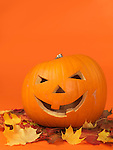 Carved smiling pumpkin on colorful fall leaves. Jack-o'-lantern Halloween symbol. Isolated on orange background.