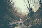 A young girl wearing a flowery raincoat standing alone on a rock beside a stream in woodland in winter