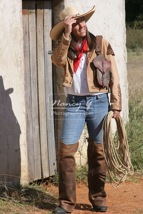 A cowgirl standing in front of a stucco building