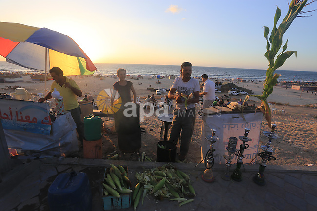 A Palestinian man sells corns at his stall along the sea front on Sep. 05, 2014. Photo by Mohammed Asad