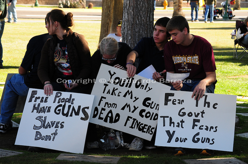 """Phoenix, Arizona. January 19, 2013 - A group of demonstrators hold signs opposing gun control during Saturday's rally in Phoenix. As President Barack Obama proposed new gun regulations last week, gun owners demonstrated against it with national """"Guns Across America"""" rallies to defend the Second Amendment. Dozens showed up at the Arizona State Capitol, many of them carrying weapons. Photo by Eduardo Barraza © 2013"""
