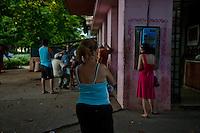 Cuba , l'Avana, quartiere Vedado, coda per telefonare, una donna vestita di rosso telefona e un'altra attende