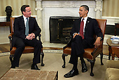 U.S. President Barack Obama (R) talks to British Prime Minister David Cameron (L) during a meeting in the Oval Office of the White House March 14, 2012 in Washington, DC. Cameron is on a three-day visit to the U.S. and he is expected to have talks with Obama on the situations in Afghanistan, Syria and Iran. .Credit: Alex Wong / Pool via CNP