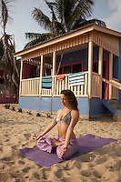 Belize, Central America - Mid thrities woman practices yoga infront of a private beach house at the end of the Placencia spit.