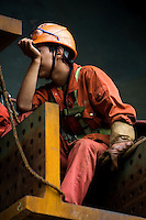 A worker is tired on a tower section of Self-Anchored Suspension bridge being assembled outside the workshops of Shanghai Zhenhua Port Machinery Co. Ltd. (ZPMC), on Changxing Island, Shanghai, on September 29, 2009. Photo by Lucas Schifres/Pictobank