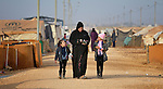 A mother walks her two girls to school in the Zaatari Refugee Camp, located near Mafraq, Jordan. Opened in July, 2012, the camp holds upwards of 50,000 refugees from the civil war inside Syria, but its numbers are growing. International Orthodox Christian Charities and other members of the ACT Alliance are active in the camp providing essential items and services.