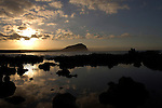 Reflections of clouds and the sun rise in the Canarian waters, In the background is the rock known as red mountain, El Medano, Tenerife, Canary Islands.