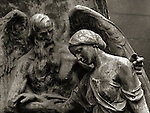 Cemetery statue of two figures with elderly male consoling younger female figure in sad pose