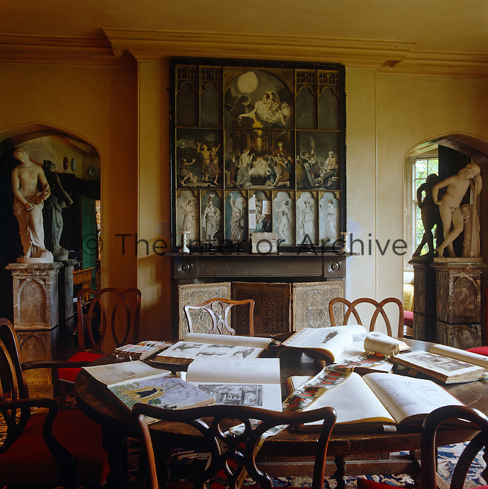 Sketch books and books of prints lie open on the circular dining table