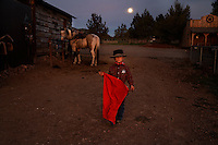 Ready for action with his red cape, sheriff's badge and mustang Paiute, a young boy stands under the full moon at the Lauman ranch.  Tanner Lauman has won many awards riding his mustang.<br /> <br /> Kitty Lauman (his mother)trains mustangs--as she says working with the horses, not against them.  They have a ranch in Prineville, OR.<br /> <br /> Kitty, her husband Rick and their children, Josie, 2 &frac12;,  and Tanner, 5,  ride mustangs. Kitty Lauman started her career as a horse trainer at the tender age of nine, under the guidance of her grandfather, John Sharp. <br /> <br /> She later became a top Pee Wee and High School Rodeo contestant, competing in barrel racing and cutting, among other events. Despite her mother's assertion that &quot;horse training isn't a real job,&quot; Kitty managed to make a living as a trainer after high school (and her mom now helps out with the business!) <br /> <br /> Kitty won the title of Miss Rodeo Oregon in 1994, and since then, has continued to expand her horse training knowledge and experience.  She placed second in the Extreme Mustang Makeover, a national competition in 2008.