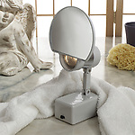 A lighted mirror sits atop a marble counter-top.