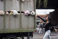 "Banksy enthusiasts flock to the trendy Meatpacking District in New York on Friday, October 11, 2013 to see the eleventh installment of Banksy's art, ""The Sirens of the Lambs"". This particular sculptural piece consists of a slaughterhouse truck filled with bleating plush animals, controlled by puppeteers, which were driven around by a driver, who remained in character. The elusive street artist is creating works around the city each day, during the month of October accompanied by a satirical recorded message parodying a museum tour which you can get by calling the number 1-800-656-4271 followed by  # and the number of artwork.  (© Frances M. Roberts)"