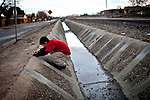 Ten-year-old Benito Tirjeron jumps over a drainage ditch on the edge of the Parklawn neighborhood in Modesto, Calif., March 1, 2012.