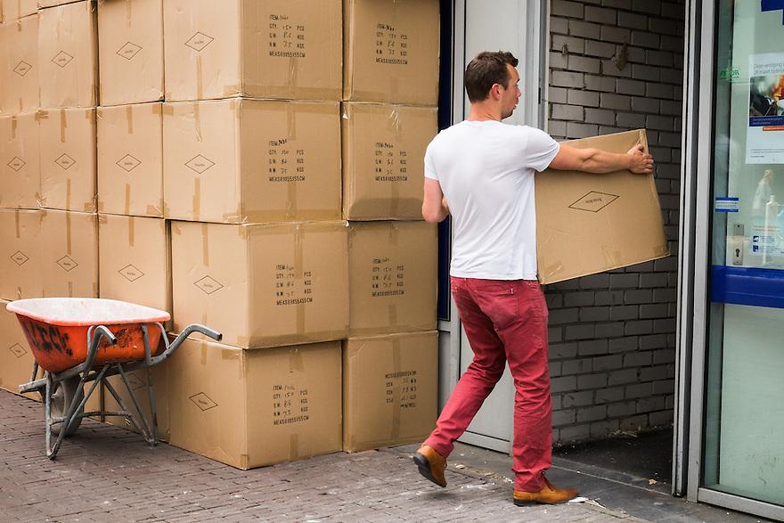 Nederland, Utrecht, 16 juni 2015 <br /> Man draagt een doos naar binnen. Buiten staat nog een enorme stapel van dezelfde dozen, die moeten nog allemaal naar binnen.  <br /> <br /> Foto: Michiel Wijnbergh