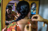 Sharda ties her mother's saree in the brothel where they live with their mother, a commercial sex worker, in the Mau Red Light area in Mau, Uttar Pradesh, India on 17 November 2013. Commercial Sex Worker's children growing up in the brothels are pampered and groomed to be the next generation of prostitutes, traffickers or pimps, however, Sharda is being married off into a community outside, sealing her future away from this vicious cycle, and her mother is keen to get all her 5 children out of the prostitution community.