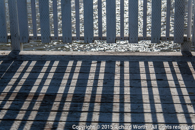 A fishing pier on a late afternoon casts shadows while the water glistens.
