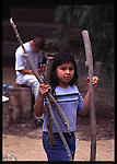 Gabrieleno/Tongva girl in jeans and a t-shirt carries sticks to help build a traditional house in Heritage Park, Santa Fe Springs, CA