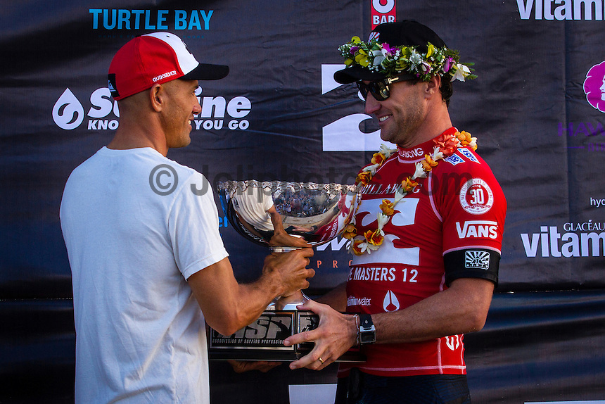HONOLULU, Oahu, Banzai Pipeline - (Friday, December 14, 2012) 2011  Kelly Slater (USA)   the 11 World Champion hands the World Tilte trophy to 2012 World Champion Joel parkinson (AUS).  -- The Billabong Pipe Masters wrapped up today with the crowning of the 2012 World Title going to Joel Parkinson (AUS) after Josh Kerr (AUS) defeated Kelly Slater (USA) in the second semi final. Parkinson won the whole event when he defeated Kerr in the final.Photo: joliphotos.com
