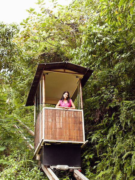 Young woman rides the funicular (or tram) at Ubud Hanging Gardens, Bali, Indonesia. The funicular runs from the main lobby to Diatas Pohon Cafe.
