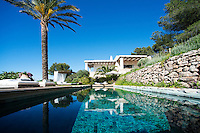 The covered terraces of the contemporary villa are reflected in the water of the outdoor swimming pool