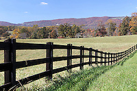 A farm fence lines the road with a view of the Blue Ridge mountains in Albemarle County, VA. Photo/Andrew Shurtleff