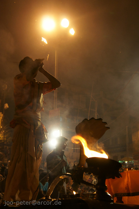 prayer ceremony at the Ganges: Aarti puja (meaning light prayer) is  a famous public ceremony in   Varanasi, India, including many rituals, also light from wicks soaked in  purified butter (ghee)  is offered.